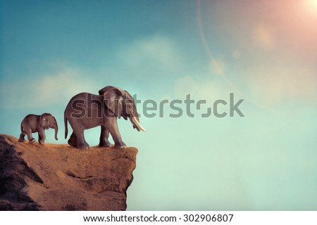 extinction concept elephant family on edge of cliff - stock photo