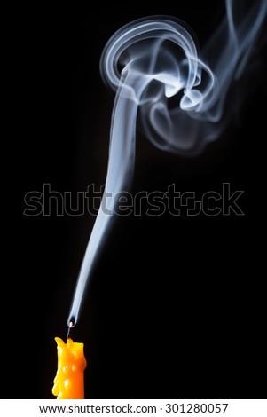 extinguished candle yellow with smoke, isolated over black - stock photo