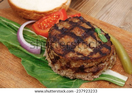 extra thick hot beef meat hamburger lunch on wooden plate with tomatoes and salad over wooden  table with cutlery and fresh sweet bun - stock photo