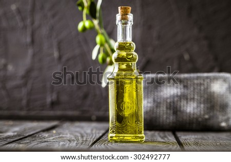 Extra virgin healthy Olive oil with fresh olives on dark wooden background - stock photo