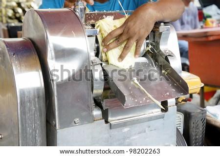 Extracting sugar cane juice. - stock photo