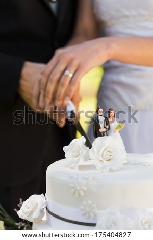 Extreme close-up mid section of a newlywed cutting wedding cake - stock photo