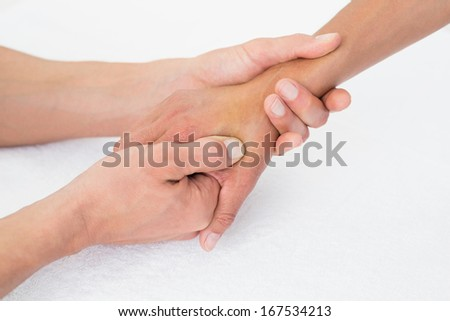 Extreme close-up of a doctor examining a female patient's hand in the medical office - stock photo