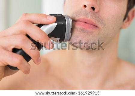 Extreme Close up of a handsome young shirtless man shaving with electric razor - stock photo