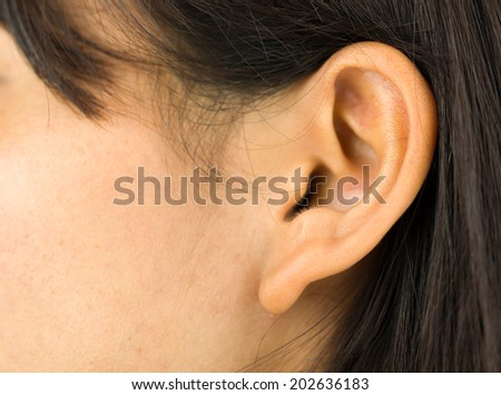 Extreme close-up of a young woman's ear - stock photo