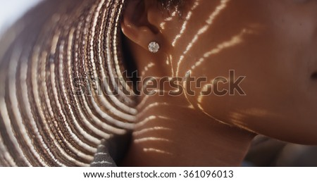 Extreme close up of Black woman with sunhat and diamond earing - stock photo