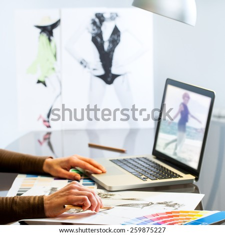 Extreme close up of Fashion Designers hands creating new collection on paper and laptop. - stock photo