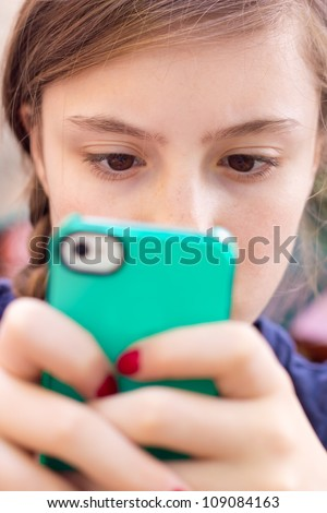 Extreme close-up of girl texting on her handheld mobile cell phone with focus on eyes. - stock photo