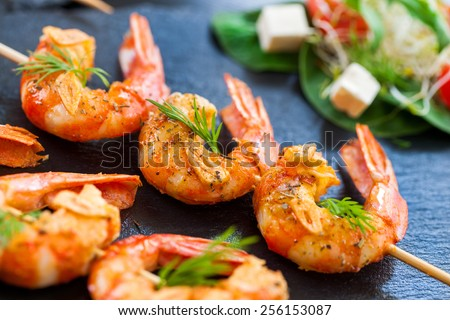 Extreme close up of grilled giant langoustine brochettes. - stock photo