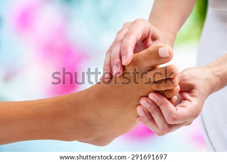Extreme close up of physiotherapist doing reflexology massage on female foot. Colorful background. - stock photo
