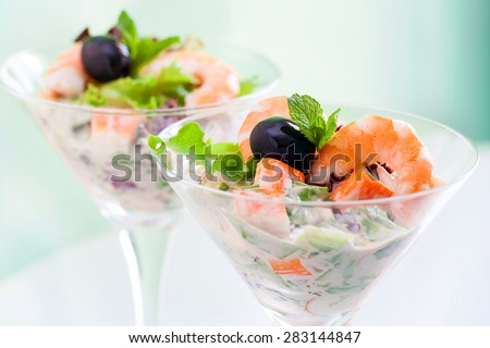 Extreme close up of shrimp and crab cocktail salad served in transparent glasses. - stock photo