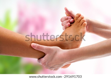 Extreme close up of therapist doing osteopathic massage on female foot. Colorful background. - stock photo