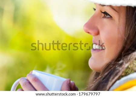 Extreme close up of young girl drinking coffee outdoors. - stock photo