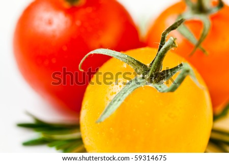 extreme closeup/macro of three cherry tomatoes with rosemary on white - stock photo