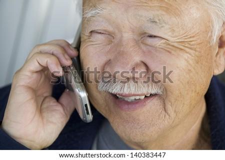 Extreme closeup of a senior man using mobile phone - stock photo