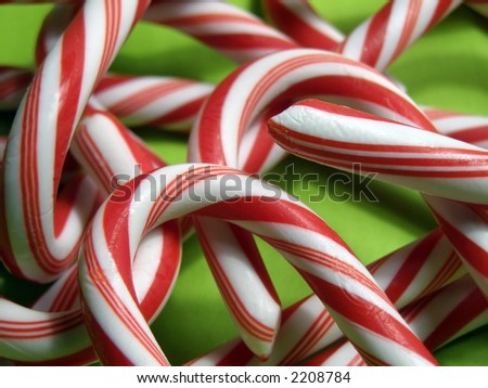 Extreme closeup of candy canes on green background. - stock photo