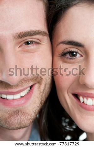 Extreme closeup of smiling young couple faces - stock photo