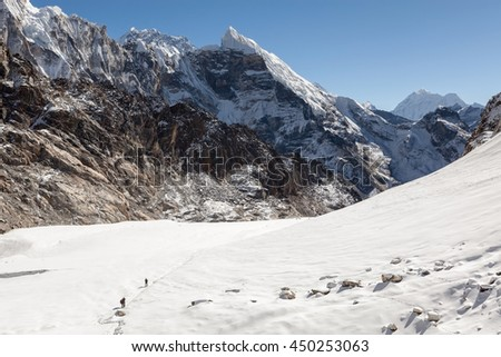 Extreme hiking concept. Group of travellers walking up the mountain through the Cho La pass, Himalayas, Nepal. Alpine adventure - mountaineers traversing a snow covered valley in winter. - stock photo