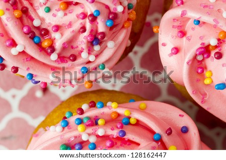 Extreme macro close-up shot of a strawberry cupcake with lots of sprinkles. - stock photo