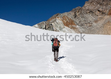 Extreme solo hiking concept. Single traveller walking up the mountain in deep snow with big heavy backpack and trekking pole. Alpine adventure - mountaineer traversing a snow covered valley in winter. - stock photo