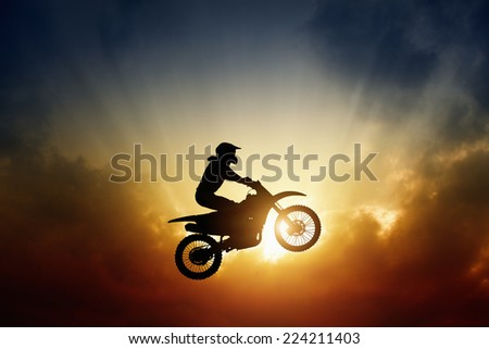 Extreme sports background - silhouette of biker jumping on motorbike on sunset - stock photo