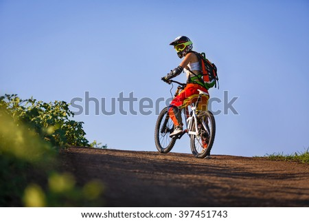 Extreme summer sports - young sportive strong woman or sportswoman riding downhill on mountain bicycle in helmet and other protective gear - stock photo