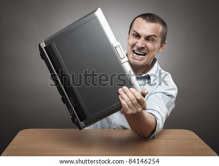 Extremely angry businessman smashing his laptop on the desk - stock photo