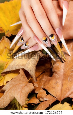 extremely long nails with nail-art and crystal jewellery,  - stock photo