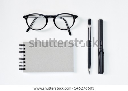 Eye glasses, blank notepad, and mechanical pencil on the table - stock photo