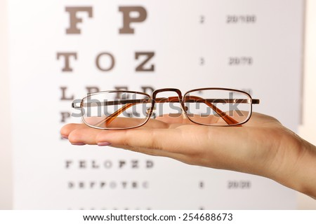Eye glasses in female hand on eyesight test chart background - stock photo