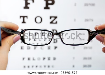 Eye glasses in female hands on eyesight test chart background - stock photo