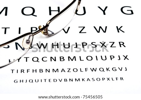 Eye glasses on examination paper - stock photo