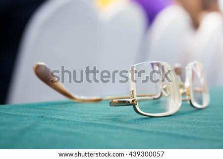 Eye glasses on green cloth. - stock photo