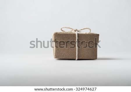 Eye level shot of a simply packaged brown cardboard box with lid, tied to a bow with string.  Off white background. - stock photo