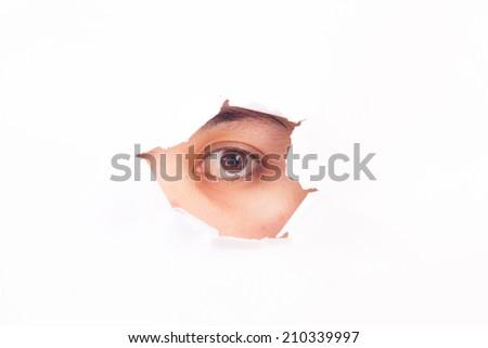 Eye looking through hole. Isolated on white - stock photo