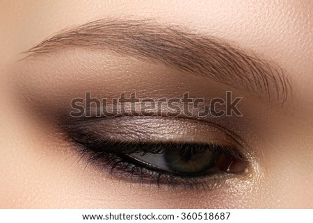 Eye makeup. Beautiful eyes make-up. Holiday makeup detail. Long eyelashes. Close-up shot of female eye make-up in smoky eyes style - stock photo