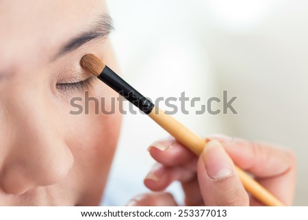 eye makeup with brush on pretty woman face - stock photo