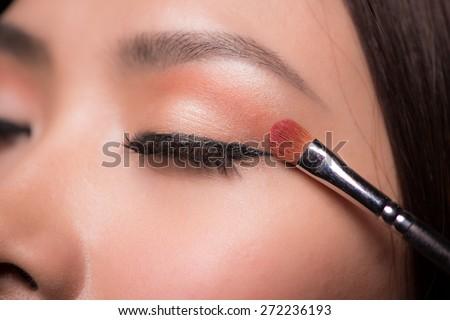 Eye makeup woman applying eyeshadow powder. Makeup. Make-up. Eyeshadows. Eye shadow brush - stock photo