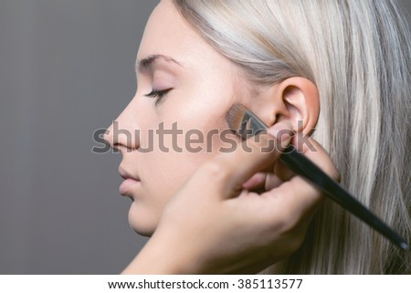 Eye makeup woman applying eyeshadow powder with make up brush - stock photo