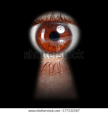 eye peeking through a keyhole concept for curiosity, stalker, surveillance and security - stock photo
