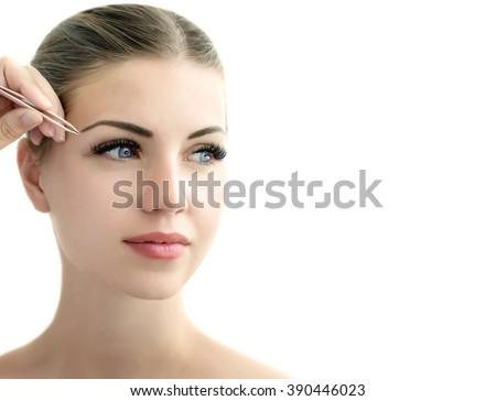 Eyebrow correction. Eyebrow correction procedure for the model with long eyelashes - stock photo