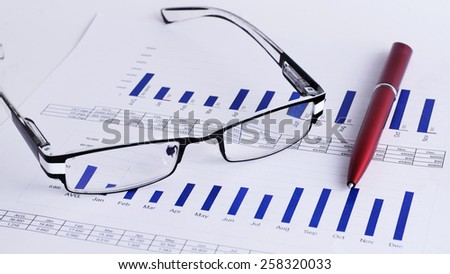 Eyeglass and pen on Chart for Business concept - stock photo