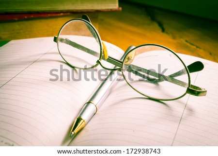 Eyeglasses and pen on book,vintage light style. - stock photo