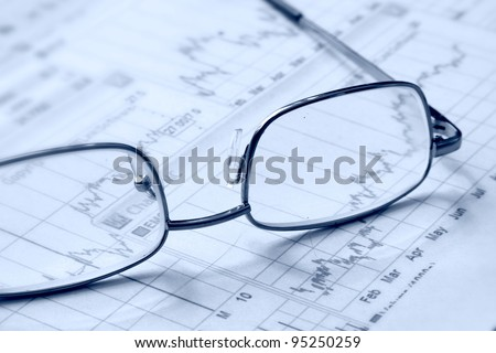 Eyeglasses laying down on a business document - stock photo