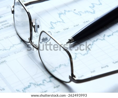 Eyeglasses lying down on a business document - stock photo