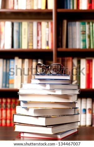 Eyeglasses lying on the opened book and many other books on background - stock photo