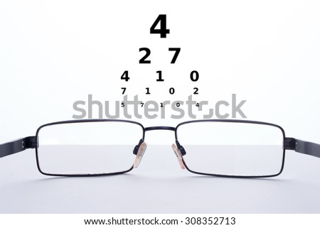 Eyeglasses on a table and numbers for a Snellen test on a white background - stock photo