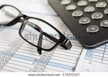 Eyeglasses over business documents - stock photo
