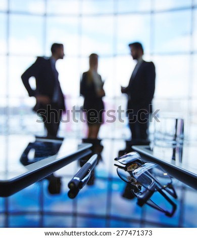 Eyeglasses, pen and touchpads at workplace with three employees having meeting on background - stock photo