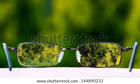 Eyeglasses placed on table with green nature background - stock photo